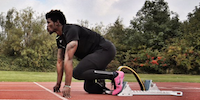 Athlete with Prosthetic Leg On Starting Blocks