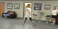 Woman Double Amputee Walking In Prosthetic Limbs During Therapy